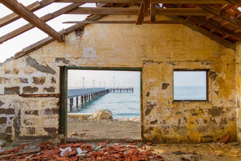 Pieransicht durch aufgegebenes Hausfenster durch den Strand lizenzfreie stockfotografie