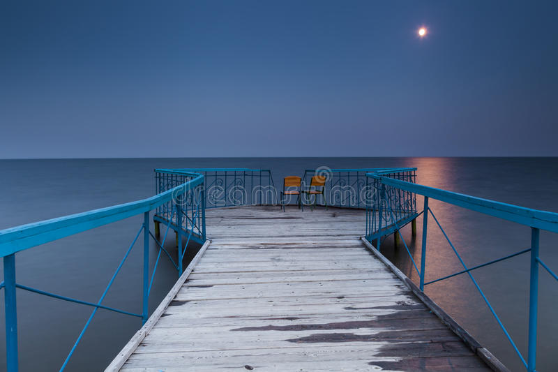 Pierce with two chairs. Against a nightscape stock photos