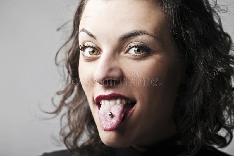Piercing. Beautiful woman sticking out her tongue and showing her piercing stock photo