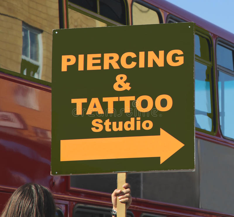 Piercing and Tattoo sign. A woman holding a piercing and tattoo sign royalty free stock photos
