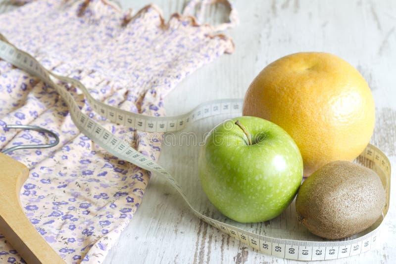 Pierda el peso al concepto de la ropa con el vestido y las frutas adietan fotos de archivo libres de regalías