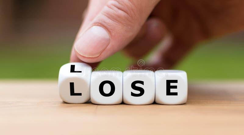 Pierda para perder la situación La mano da vuelta a dados y cambia la palabra fotografía de archivo