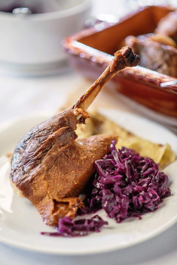 Pierna asada del ganso con las crepes de la col roja y del potatoe en la placa blanca, comida tradicional fotografía de archivo