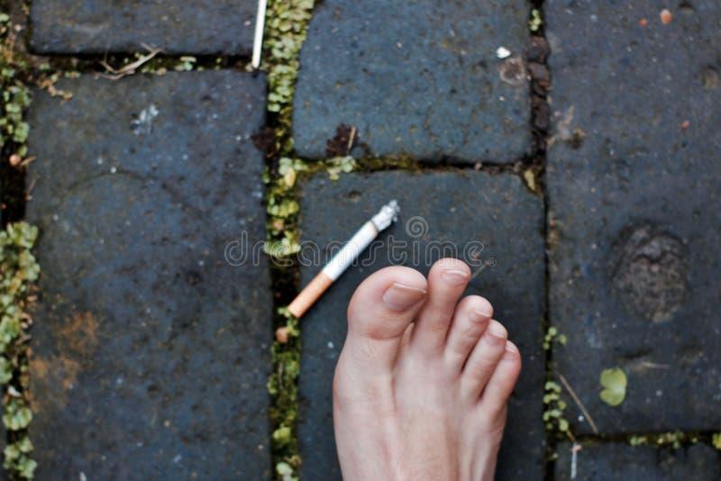 Pierna cerca del cigarrillo imágenes de archivo libres de regalías