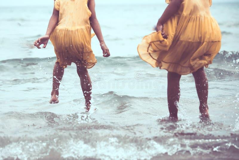 Pierna de dos muchachas asiáticas del pequeño niño que saltan y que juegan en la playa foto de archivo