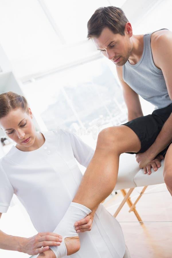 Pierna de examen del fisioterapeuta del hombre con el vendaje fotos de archivo