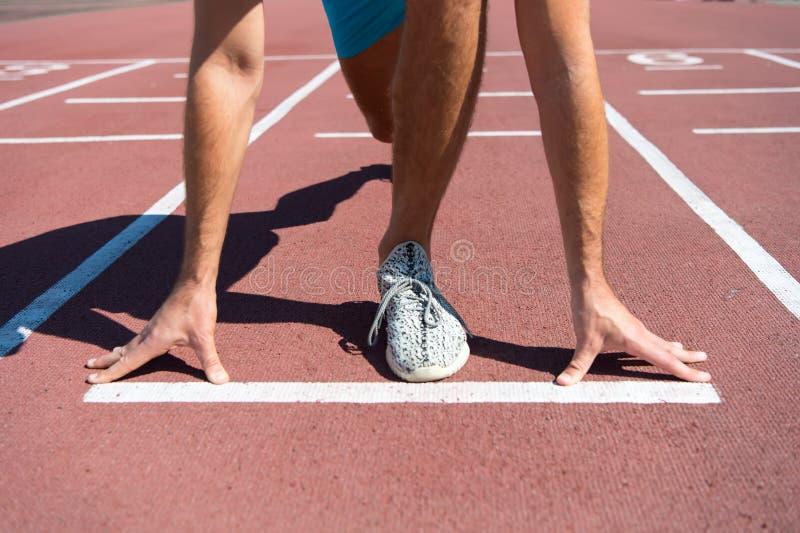 Pierna de la competencia del comienzo del hombre del hombre que corre en la pista de la arena foto de archivo libre de regalías