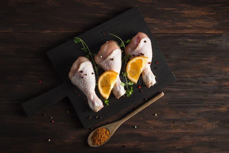 Pierna de pollo cruda con las naranjas y el tomillo y una cucharada de especias imagen de archivo
