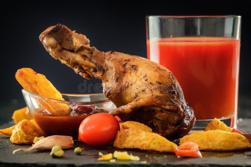 pierna de pollo frito con las patatas, verduras, tomates, pimienta, salsa en un fondo negro Un vidrio de jugo de tomate foto de archivo libre de regalías