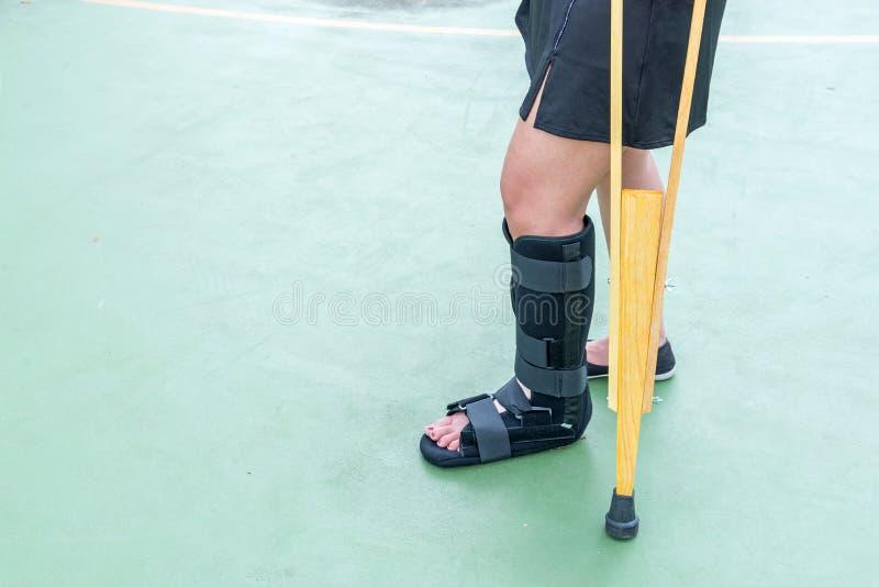 pierna dolorosa de la ropa de deportes de la mujer de lesión que lleva con el molde de la pierna y w imagen de archivo