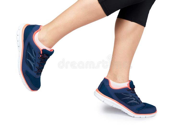 Pierna femenina apta en el zapato del deporte aislado en el fondo blanco foto de archivo
