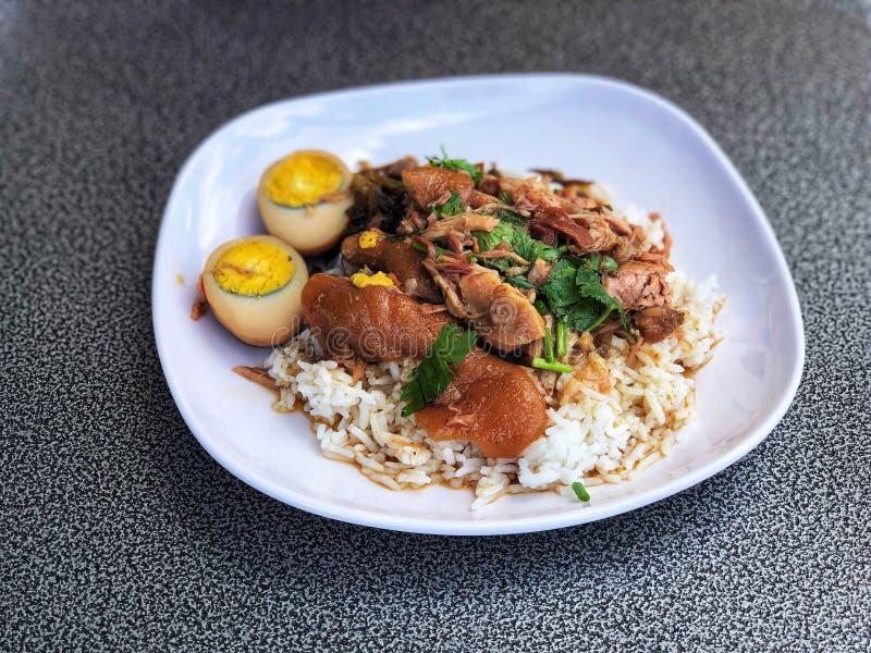Pierna guisada del cerdo con los huevos en el arroz en el plato blanco, delicioso de la comida tailandesa foto de archivo
