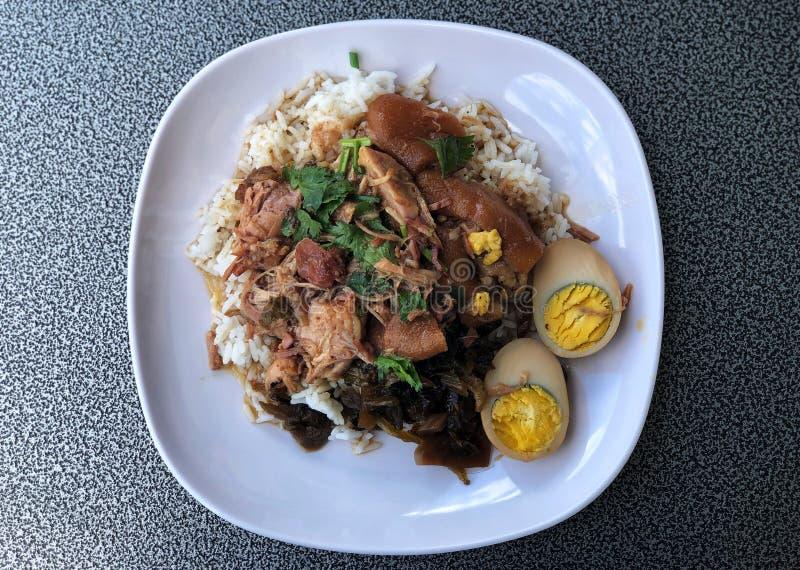 Pierna guisada del cerdo con los huevos en el arroz en el plato blanco, delicioso de la comida tailandesa fotografía de archivo libre de regalías