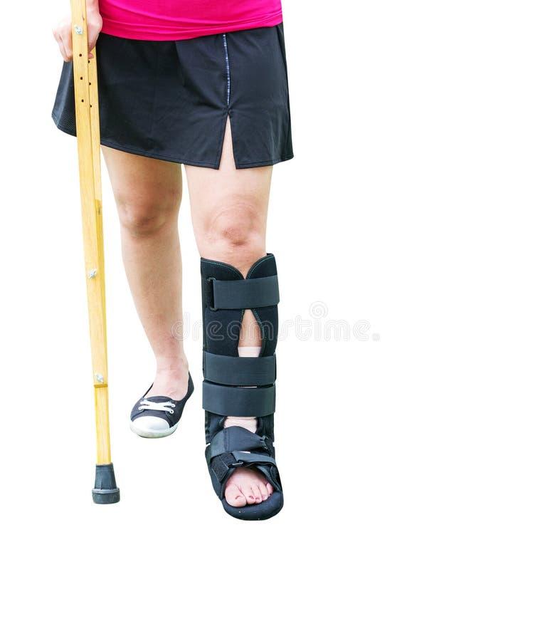 pierna quebrada de la mujer y muleta heridas con para el paseo aislado en w imagenes de archivo