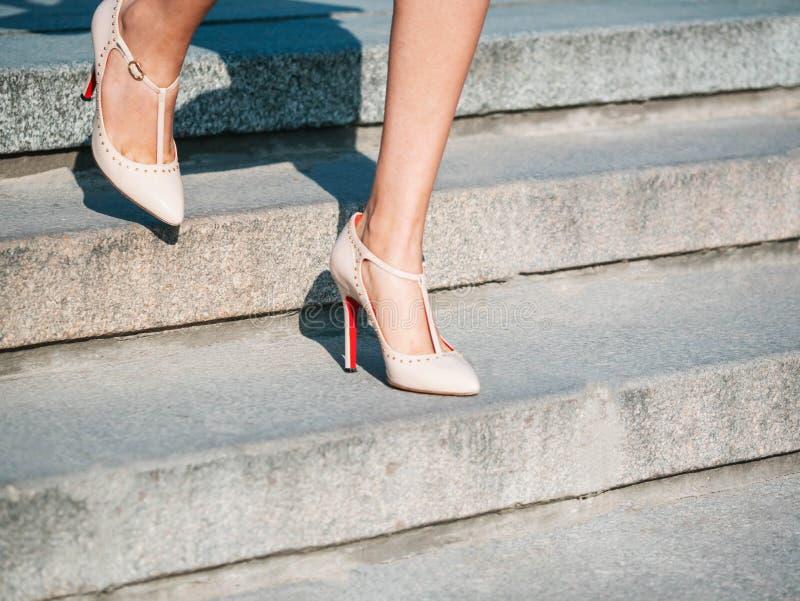 Piernas atractivas con los altos zapatos de tacón beige en las escaleras de piedra de la ciudad Mujer de negocios que camina en b imágenes de archivo libres de regalías