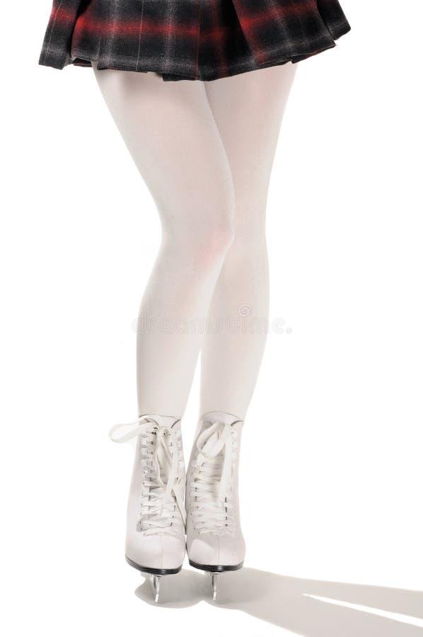 Piernas atractivas de la figura patinador en los patines de hielo blancos foto de archivo