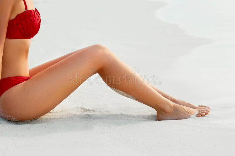 Piernas atractivas de la mujer de Bikin del bronceado que relajan acostarse cerca de la playa Skincare de la belleza imagen de archivo
