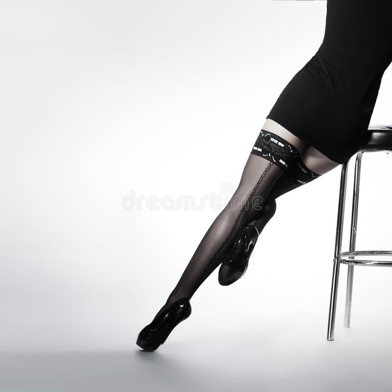 Piernas atractivas de una mujer joven en medias negras fotos de archivo