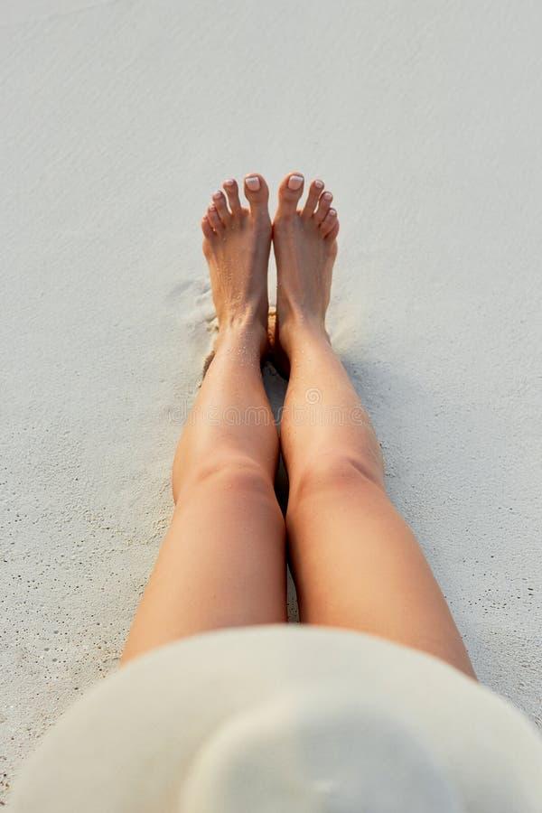 Piernas atractivas hermosas de las mujeres en la playa Cuidado de piel y protección Sun Balneario Concep fotografía de archivo libre de regalías