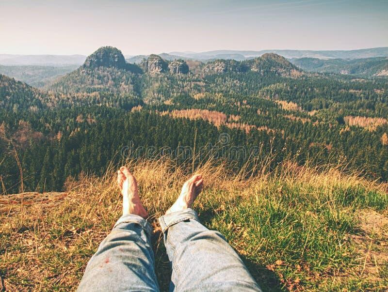 Piernas cansadas de los caminantes sin los zapatos viajero que se relaja imagen de archivo libre de regalías