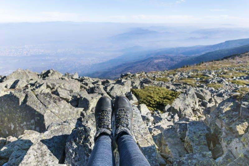 Piernas con caminar botas en un fondo de la montaña foto de archivo libre de regalías