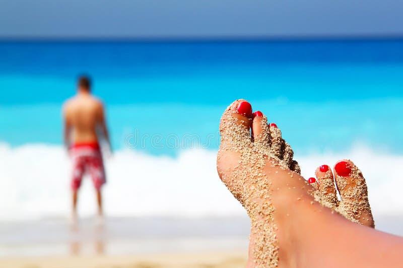 Piernas cruzadas en la playa imagen de archivo