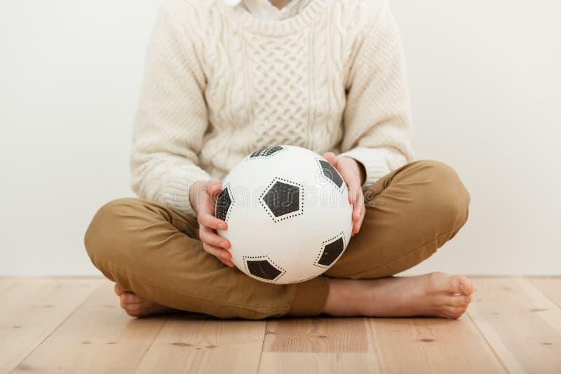 A piernas cruzadas muchacho descalzo que sostiene un balón de fútbol fotos de archivo libres de regalías