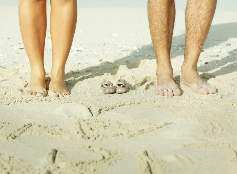 piernas de la madre y del padre con los pequeños zapatos de bebé foto de archivo libre de regalías