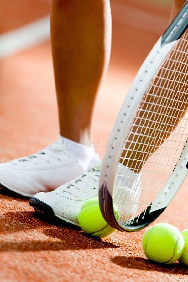 Piernas de la muchacha juguetona cerca de la raqueta de tenis foto de archivo