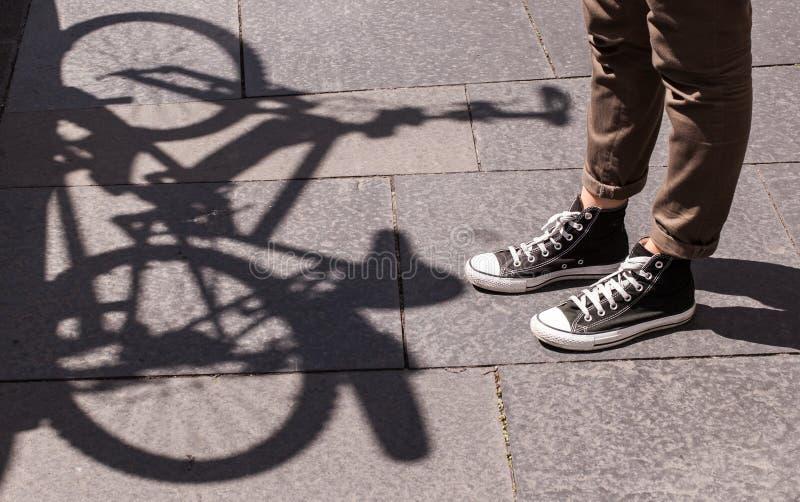Piernas de la muchacha que llevan risitas negras y los pantalones marrones flacos delante de la sombra de una bicicleta imágenes de archivo libres de regalías