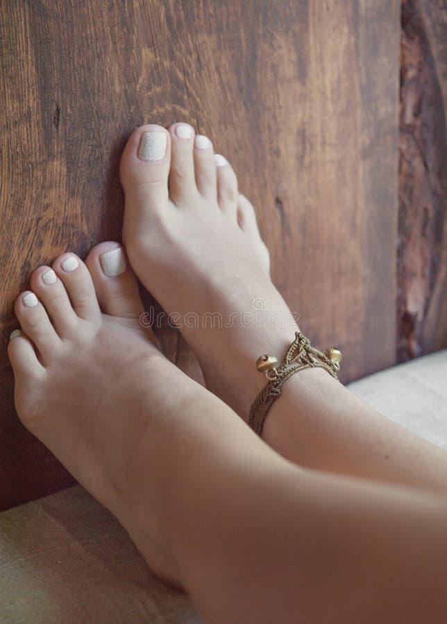 Piernas de la mujer con la pulsera imagenes de archivo