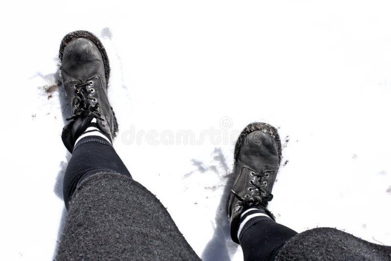 Piernas de la mujer con los pies en la nieve fotografía de archivo libre de regalías