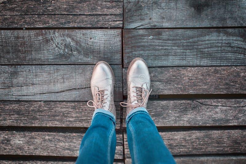 Piernas de la mujer con los zapatos en bridgeconce de madera foto de archivo libre de regalías