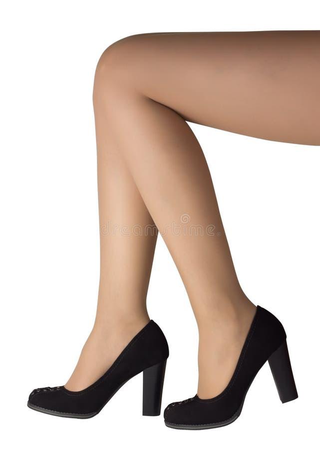 Piernas de la mujer con los zapatos negros del alto talón imagen de archivo