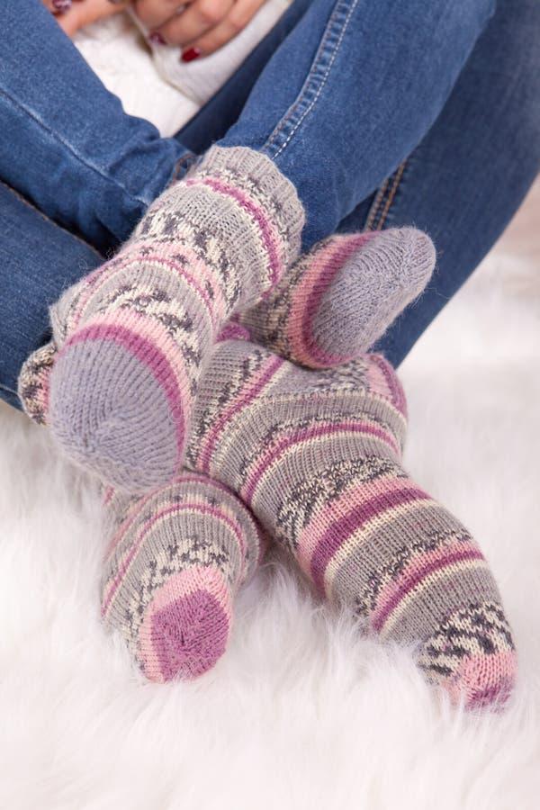 Piernas de la mujer en calcetines rosados de lana hechos punto primer imagen de archivo