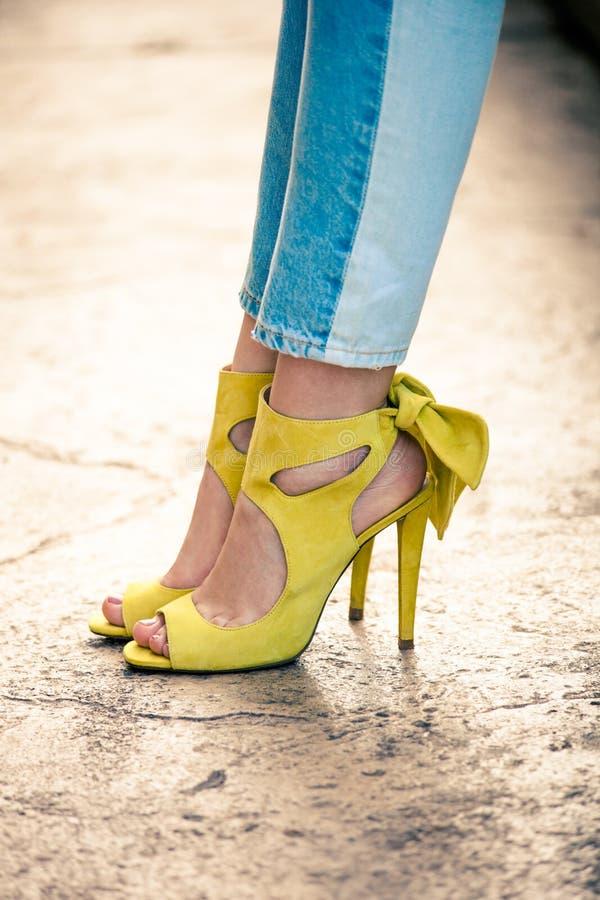 Piernas de la mujer en las sandalias amarillas de cuero del tacón alto al aire libre en ciudad imagen de archivo