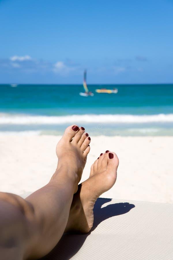 Piernas de la mujer en silla de playa foto de archivo