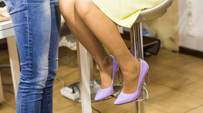 Piernas de la mujer en zapatos púrpuras del tacón alto dentro fotos de archivo