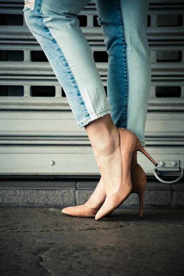 Piernas de la mujer en zapatos y tejanos del tacón alto en ciudad imágenes de archivo libres de regalías