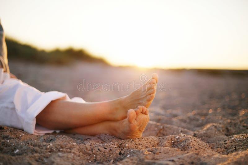 Piernas de la mujer mayor que se sientan en la playa fotografía de archivo