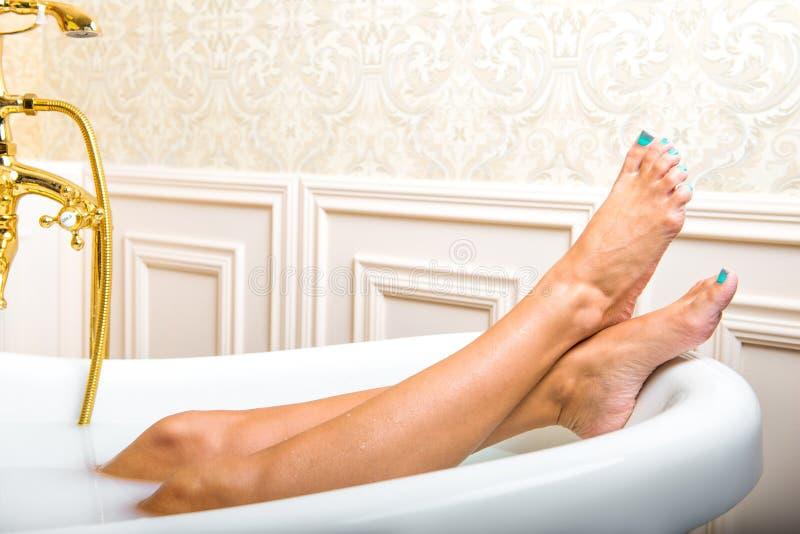 Piernas de la mujer que mienten en la bañera blanca foto de archivo