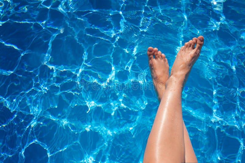 Piernas De La Mujer En Piscina Del Agua Azul Foto De Archivo