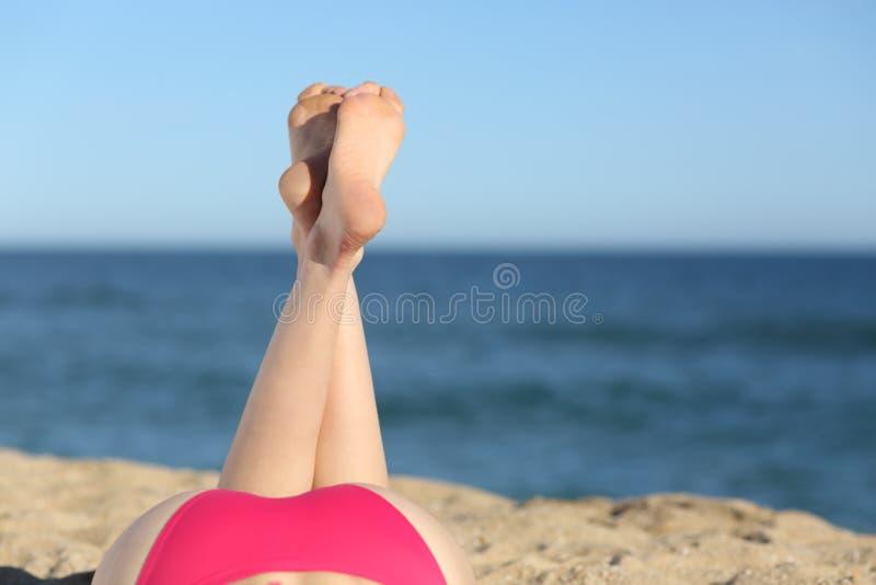 Piernas de la mujer que toman el sol en la playa que se acuesta fotografía de archivo libre de regalías