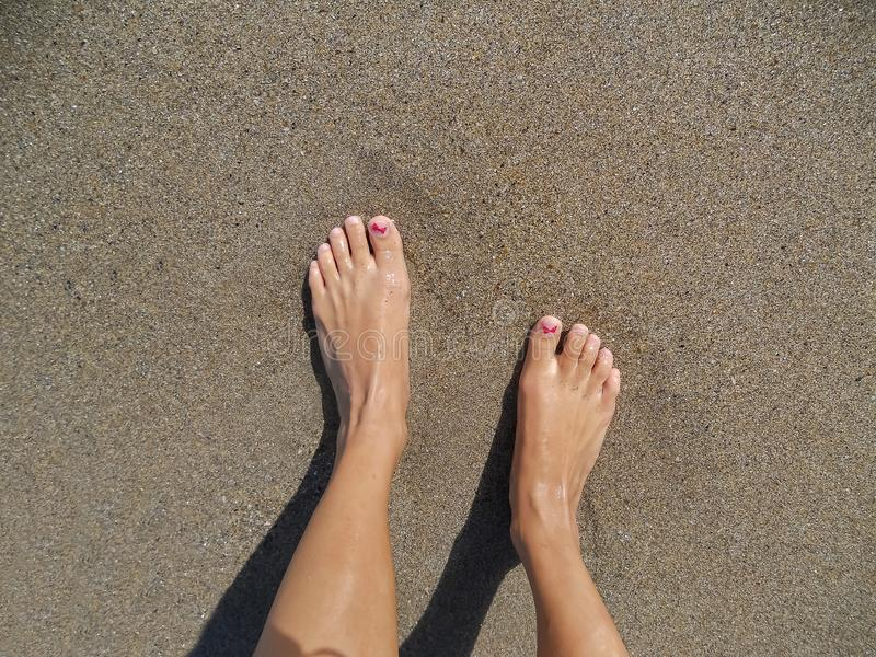 Piernas de las mujeres jovenes que se colocan en la arena en la playa fotografía de archivo libre de regalías