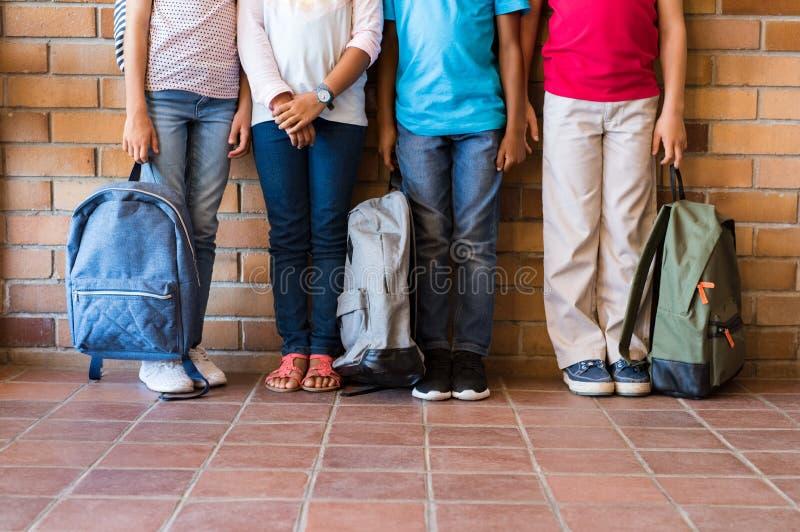 Piernas de los niños con las mochilas en la escuela fotos de archivo