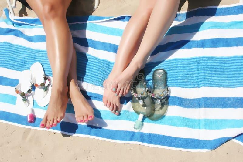 Piernas de mujeres en la playa imagen de archivo libre de regalías