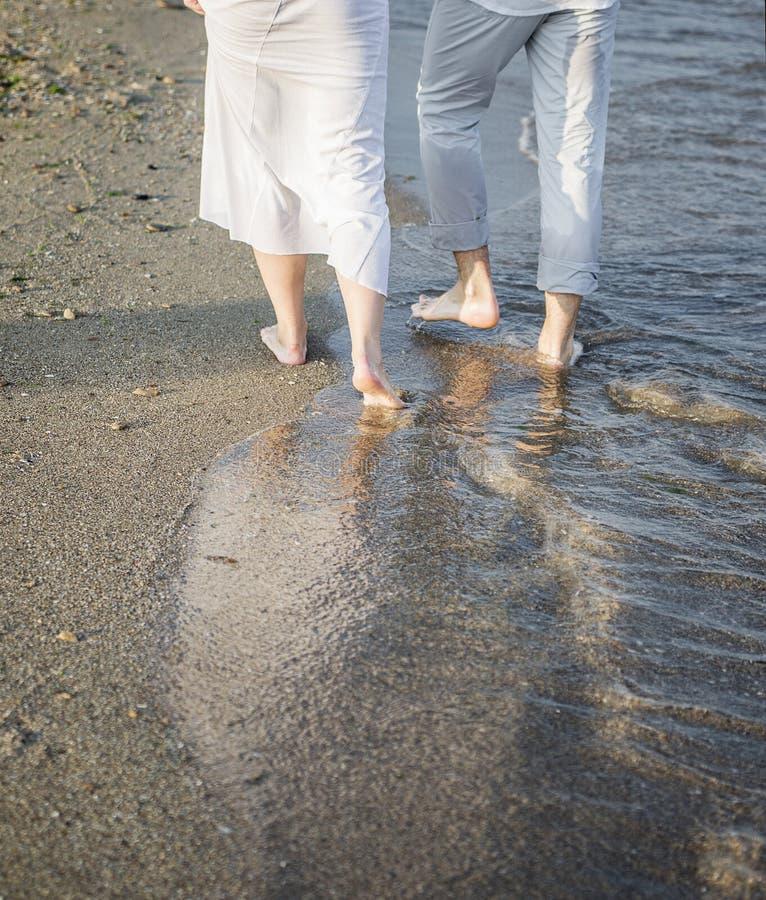Piernas de pares en la playa de la arena fotografía de archivo libre de regalías