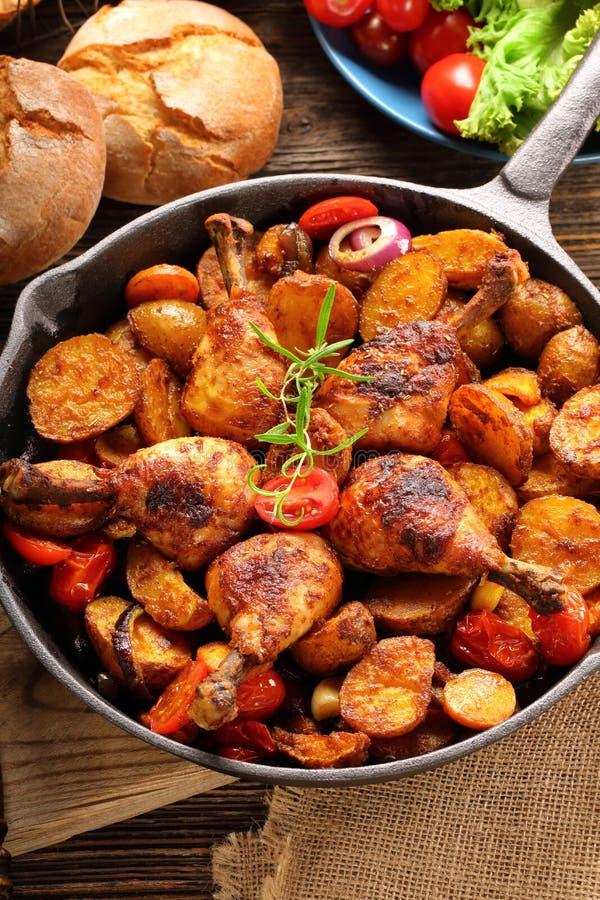 Piernas de pollo asadas con la patata cocida en el sartén foto de archivo libre de regalías