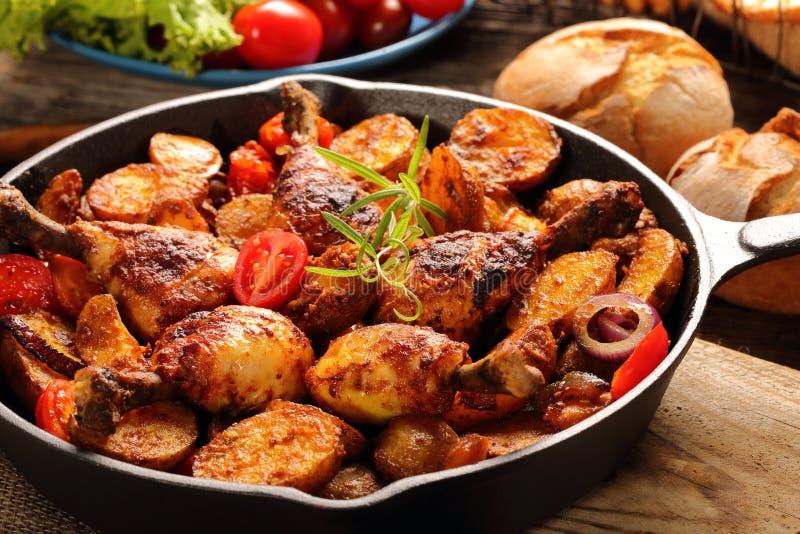 Piernas de pollo asadas con la patata cocida en el sartén fotografía de archivo libre de regalías