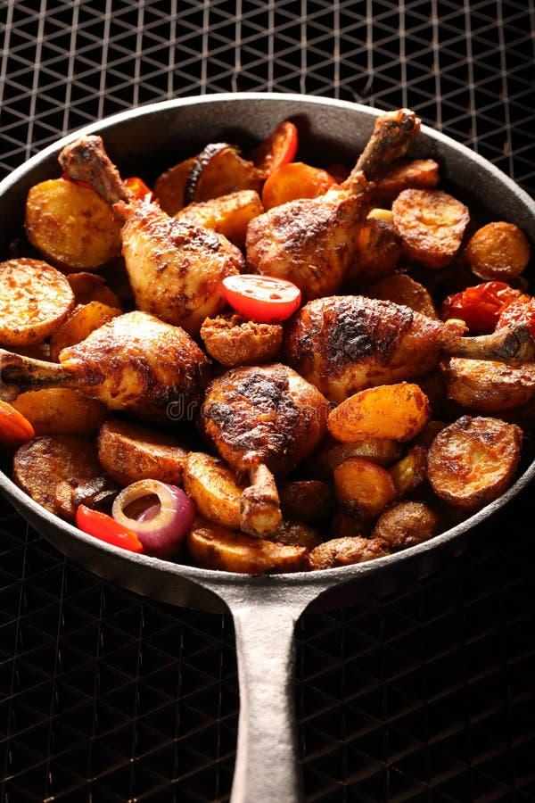 Piernas de pollo asadas con la patata cocida en el sartén fotos de archivo